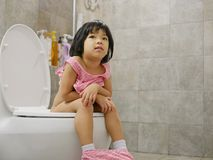 Little Asian baby girl being happy to be able to get on and use adult size toilet bow by herself successfully royalty free stock photo
