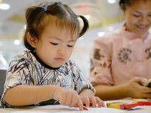Little Asian baby girl being left alone with crayons, while her mother ignoring her and solely focusing on the smartphone. Little Asian baby girl, 20 months old stock images