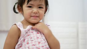 Little Asian baby girl being proud and happy as she eventually can successfully put on a shirt by herself. Little Asian baby girl, 2 years old, being proud and stock footage