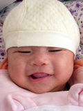 Little asian baby girl chuckling shyly. A little asian baby girl chuckling shyly with a yellow cap on head,dotted background royalty free stock photo