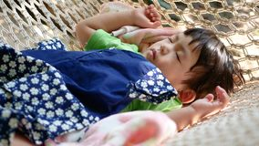 Little Asian baby girl comfortably sleeping on a hammock with the morning sunlight. Little Asian baby girl, 23 months old, comfortably sleeping on a hammock with stock video