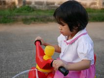 Little Asian baby girl is concentrating on learning to ride a bicycle at home stock image