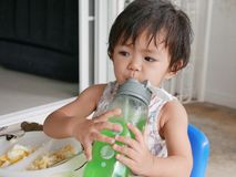 Little Asian baby girl enjoys drinking water by herself stock photos