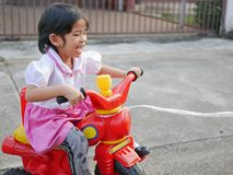 Little Asian baby girl enjoys learning to ride a bike with help pulling a rope royalty free stock photography