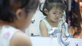 Little Asian baby girl enjoys opening a water tap and washing her hands by herself. Little Asian baby girl, 22 months old, enjoys opening a water tap and washing stock video
