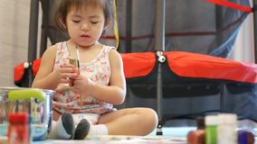 Little Asian baby girl enjoys painting at home - painting helps developing child`s hand-eye coordination. Little Asian baby girl, 2 years old, enjoys painting at stock video