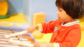 Little Asian baby girl enjoys playing a glockenspiel xylophone. Learning to play a musical instrument helps to develop sense of achievement, discipline stock footage
