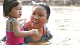 Little Asian baby girl enjoys playing water in a river with her auntie. Little Asian baby girl, 25 months old, enjoys playing water in a river with her auntie stock video footage