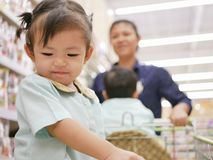 Little Asian baby girl enjoys staying in a shopping cart while her mother doing shopping at a supermarket royalty free stock photography