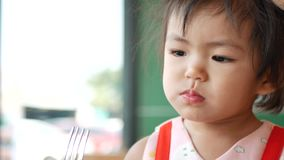 Little Asian baby girl enjoys tasting tomato ketchup by herself at a restaurant.  stock video