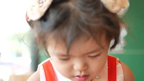 Little Asian baby girl enjoys tasting tomato ketchup by herself at a restaurant.  stock video footage