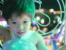 Little Asian baby girl on a ferris wheel at night stock photography