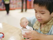 Little Asian baby girl is frustrated having a difficulty scooping hard frozen ice cream stock image