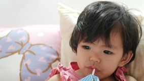 Little Asian baby girl getting drowsy while drinking milk - baby`s self soothing. Little Asian baby girl, 17 months old, getting drowsy while drinking milk stock video footage