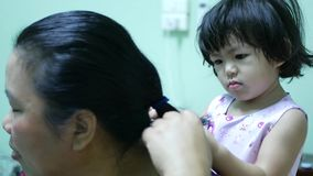 Little Asian baby girl giving her aunty`s hairs done - child development through learning to do things for others. Little Asian baby girl, 24 months old, giving stock video footage