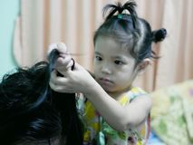 Little Asian baby girl giving her aunty`s hairs done royalty free stock photo