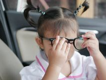 Little Asian baby girl hands putting on eyeglasses. Baby`s curiosity royalty free stock photos