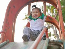 Little Asian baby girl hanging from a slide roof using overhand grip. Little Asian baby girl, 22 months old, hanging from a slide roof using overhand grip royalty free stock image