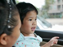 Little Asian baby girl having fun traveling with her mother by car as she learning to tell what she see during the trip. Little Asian baby girl, 33 months old stock image