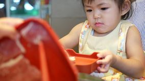 Little Asian baby girl helps her mother putting cookery ingredients into a boiling hotpot. Little Asian baby girl, 2 years old, helps her mother putting cookery stock video footage