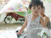 Little Asian baby girl helps her mother washing a glass sliding door royalty free stock photos