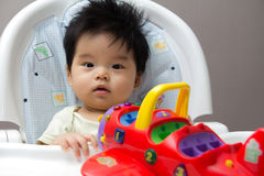 Little Asian baby girl on high chair. Playing with airplane toy Stock Images