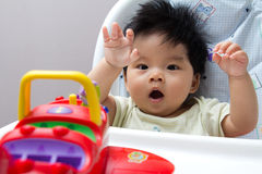 Little Asian baby girl on high chair. Playing with airplane toy Royalty Free Stock Images