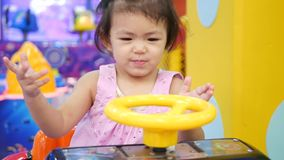 Little Asian baby girl holding a steering wheel of a driving-car arcade game and enjoyed pretending to drive it.  stock footage