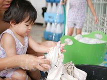 Little Asian baby girl learning to wash clothes at home royalty free stock images