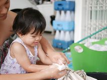 Little Asian baby girl learning to wash clothes at home royalty free stock image