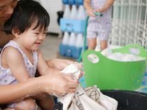 Little Asian baby girl learning to wash clothes at home. Little Asian baby girl learning, being taught by her mother, how to wash clothes by hands - child royalty free stock image