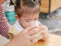 Little Asian baby girl learning to drink directly from a glass stock photo