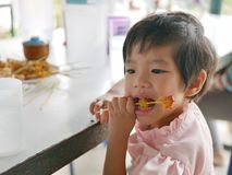 Little Asian baby girl learning to eat pork satay by herself stock images