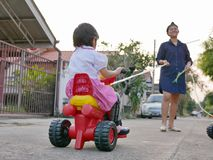 Little Asian baby girl learning to ride a bike with help from her mother. Little Asian baby girl learning to ride a bike with help from her own mother royalty free stock photos