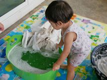 Little Asian baby girl learning to wash clothes at home. Child development through doing housework stock image