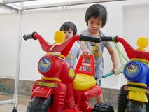 Little Asian baby girl learning to wash plastic big bikes while her little sister watching and standing nearby stock image