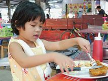 Little Asian baby girl learning and trying to eat deep-fried fish steak using a knife and fork by herself royalty free stock image