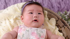 Little asian baby girl lies in basket crib in dress and headband stock video footage