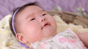 Little asian baby girl lies in basket crib in dress and headband stock footage