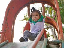 Little Asian baby girl hanging from a slide roof using overhand grip. Little Asian baby girl, 22 months old, hanging from a slide roof using overhand grip stock photography
