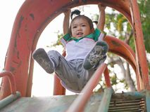 Little Asian baby girl hanging from a slide roof using overhand grip. Little Asian baby girl, 22 months old, hanging from a slide roof using overhand grip royalty free stock photos