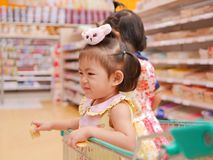 Little Asian baby girl having fun standing in a shopping cart with her sister while her mother does a shopping stock image
