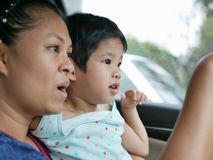 Little Asian baby girl having fun traveling with her mother by car as she learning to tell what she see during the trip. Little Asian baby girl, 33 months old royalty free stock photography