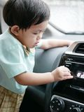 Little Asian baby girl turning a car audio player button royalty free stock images
