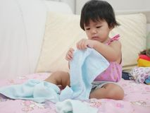 Little Asian baby girl learning to fold clothes stock photography