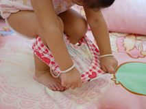 Little Asian baby girl learning to take off short pants by herself royalty free stock image