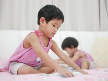 Little Asian baby girl left learning to fold clothes. Little Asian baby girl, 32 months old, left learning to fold clothes. - baby`s development through allowing royalty free stock photos