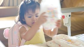 Little Asian baby girl playing / learning to arrange / stack up her diapers in pile. Little Asian baby girl, 22 months old, playing / learning to arrange / stack stock video