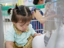 Little Asian baby girl in a shopping trolley exploring a book while waiting for her mother to do shopping stock photos