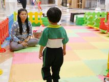 Little Asian baby girl standing in a frustrated atmosphere as she was taught and rationally dealt with by her mother stock image